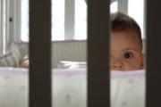 baby peering through crib slats