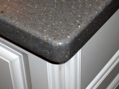 gray corian countertop on white kitchen cabinet